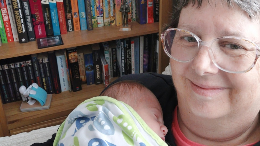 Joanne Cowan holds her newborn grandson Alex to her chest during a visit to the United Kingdom.