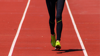 Woman running on a red track field.