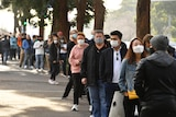 People are seen queued to receive their vaccination all are wearing face masks.