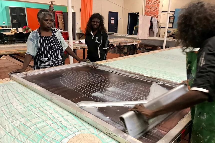 Three Aboriginal women using a screen print frame to print an image on fabric.