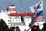 People carrying South Korean and American flags next to a ferry