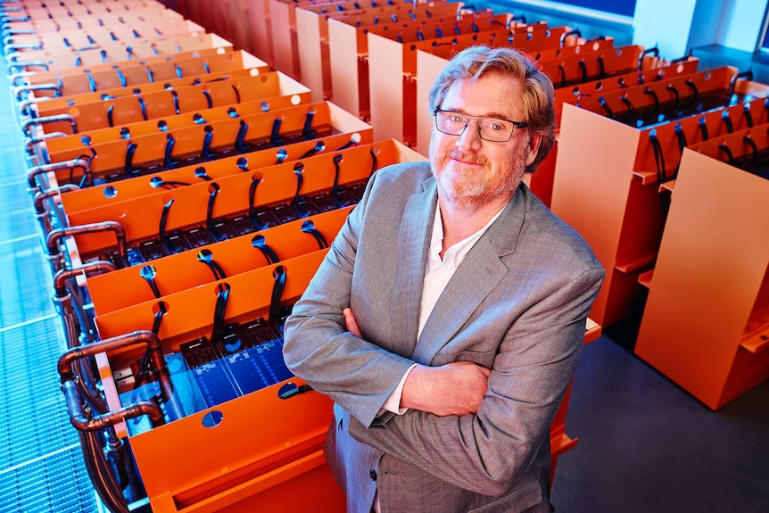 Matt Lamont standing beside a huge, orange supercomputer, with his arms crossed