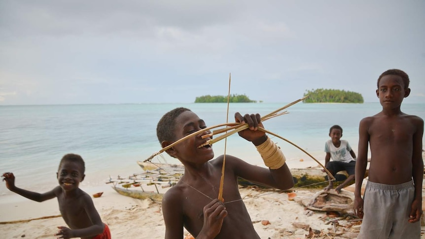 A smiling boy holds up a small toy bow and arrow with other boys in the background.