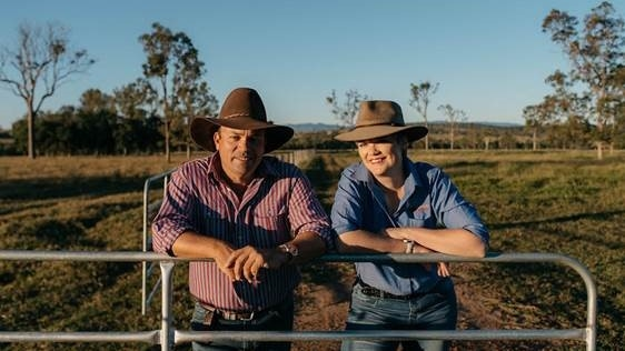 A man in an red and white striped shirt and a woman in a blue shirt lean on a gate with a paddock with trees in the background.