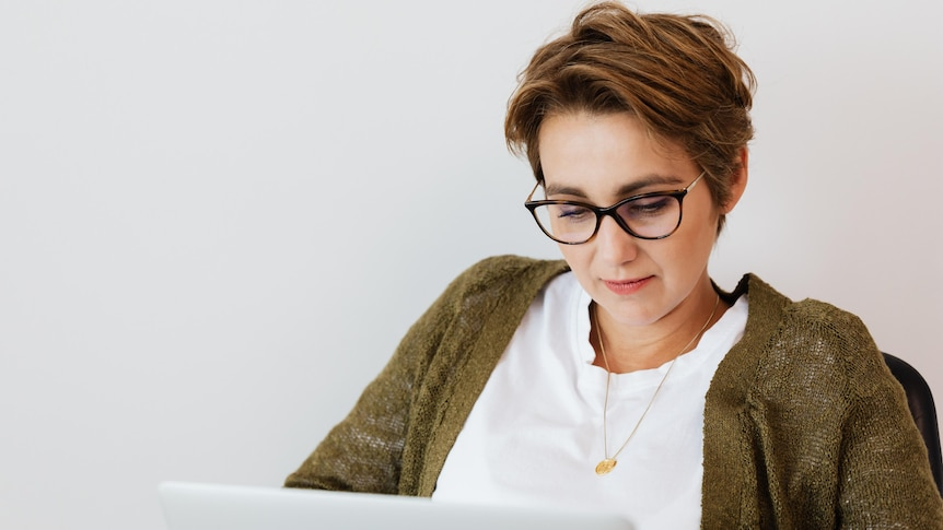 A woman wearing a green cardigan and glasses looks at a laptop screen.