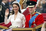 Catherine, Duchess of Cambridge, waves to the crowd as she sits alongside her husband Prince William on their wedding day.