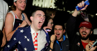 A group of young men in front of the White House struggle to contain their joy.