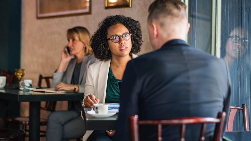 A woman sitting across from a man in a cafe setting to depict racism in online dating.