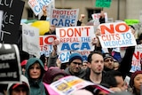 """Demonstrators hold signs reading """"Don't repeal the ACA"""" and """"No cuts to medicare"""""""