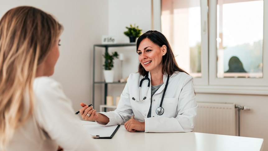 Female doctor with brown hair and white coat sitting at a desk opposite a female patient.