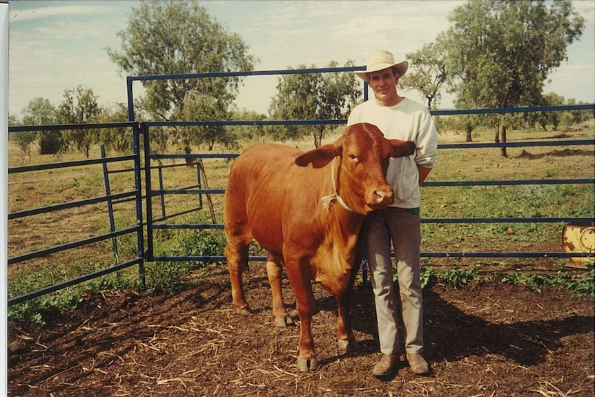 an old photo of a man with a bull