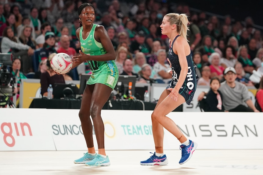 A West Coast Fever Super Netball player holds the ball while under defensive pressure from a Melbourne Vixens opponent.