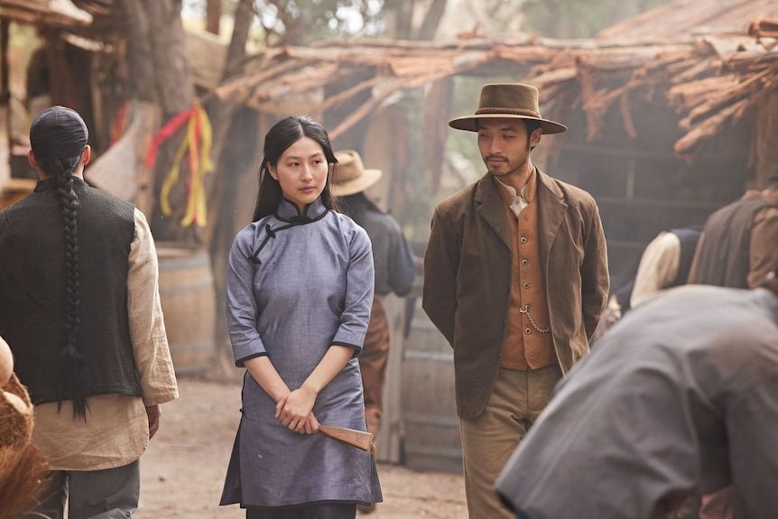 Two Chinese-Australians actors walk through an 1850s mining camp.