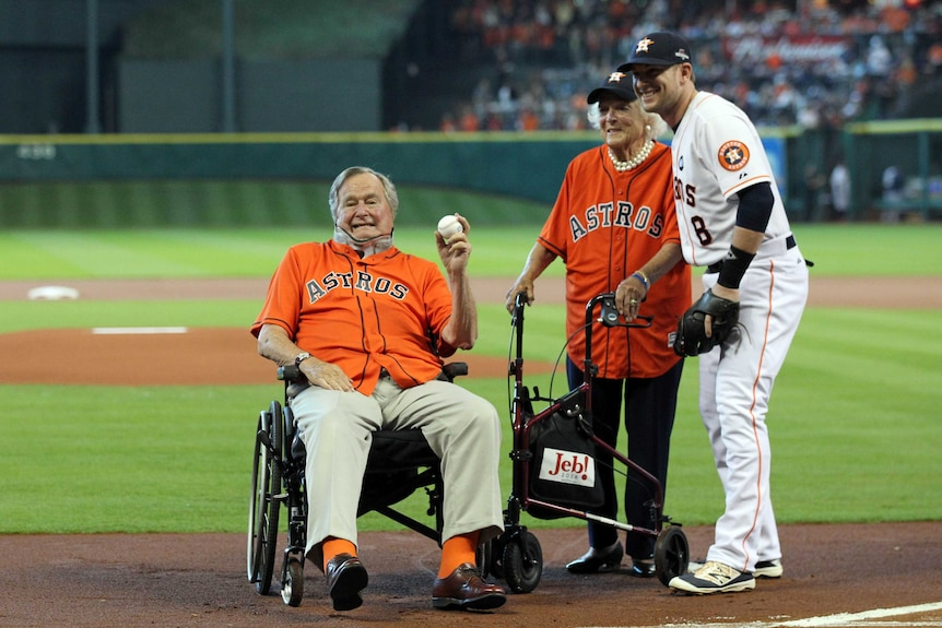 Former president George H.W Bush poses for a photo with his wife Barbara on the baseball field