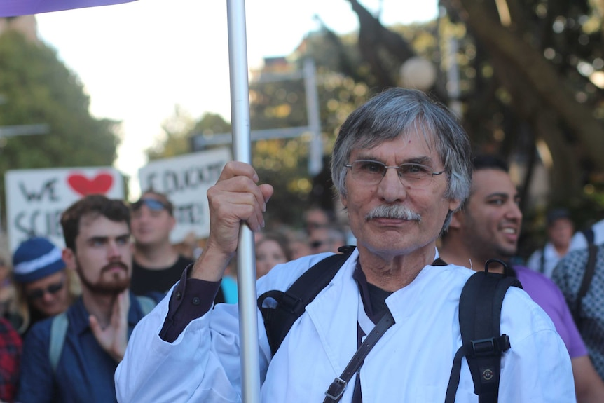 Martin Woolterding holds a sign at the march through Sydney