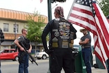 Men in tactical gear and holding huge guns chat on a street corner