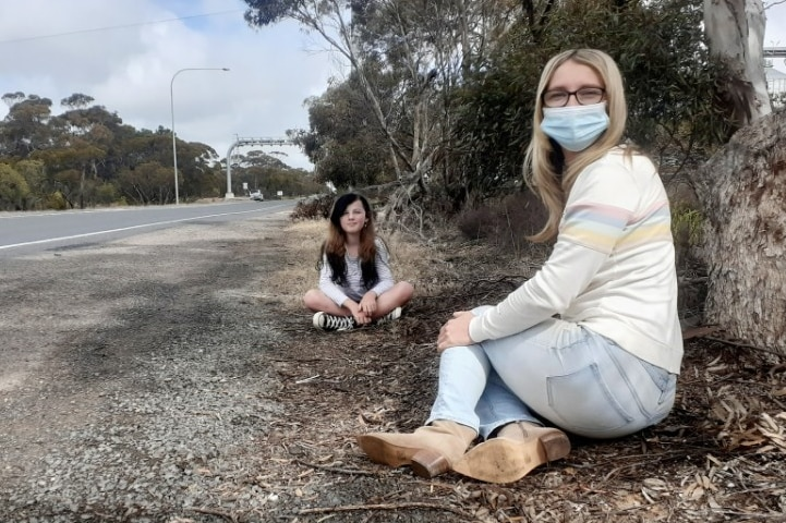 A woman wearing a face mask sits on the side of a highway with a girl behind her