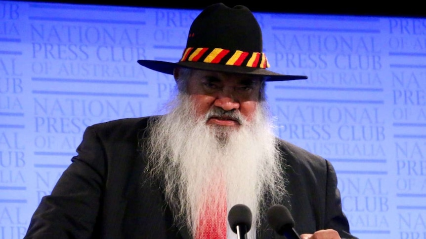 Pat Dodson wears a hat while standing at a lectern