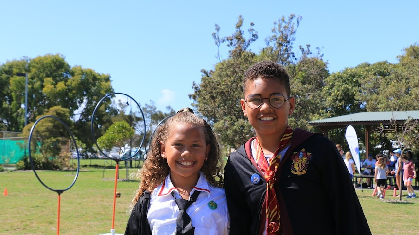 boy and girl dressed up in Harry Potter-inspired clothing at kidditch pitch