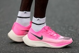 A close up of the pink running shoes worn by a runner.