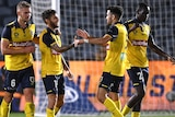 Four Central Coast Mariners players celebrate an A-League goal