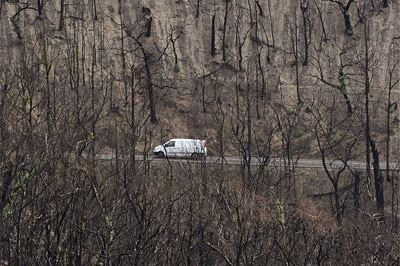 A car drives through a landscape devastated by bushfires in February near the township of Kinglake