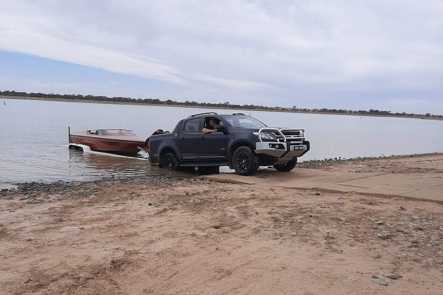 A ute pulls a boat on a trailer out of a lake.