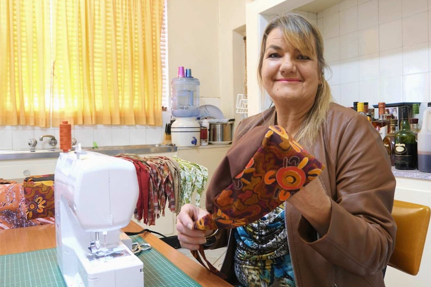 A woman holds up a cap made of fabric covered in colourful indigenous art.