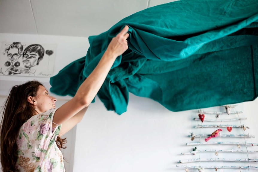 Woman with brown hair shaking a green sheet in a white room.