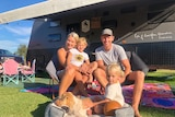 A family sitting in front of a caravan smiling.