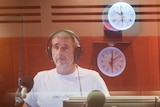 A middle-aged man with a grey goatee beard stands in the radio studio, amid several clocks reflected in the glass