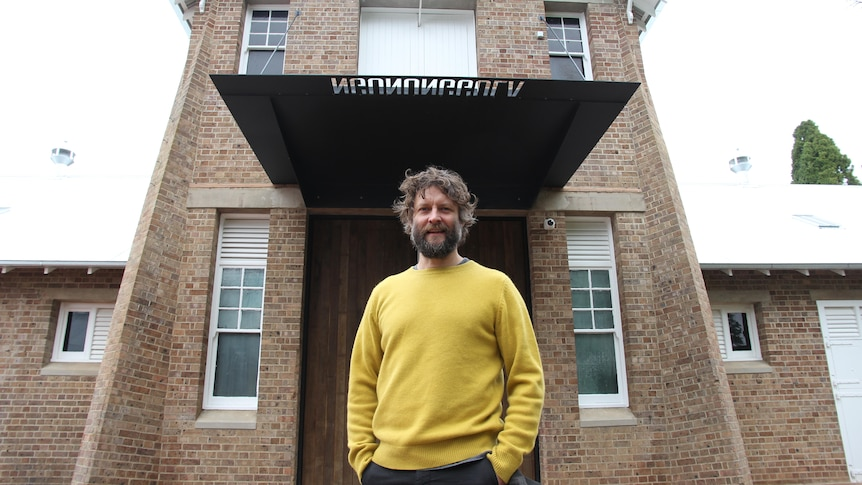 Ben Quilty wears a yellow jumper and stands out the front of the gallery's entrance.
