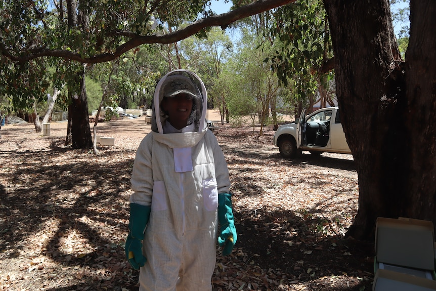 Dr Daniela Scaccabarozzi stands in a forest wearing a full beekeeping outfit