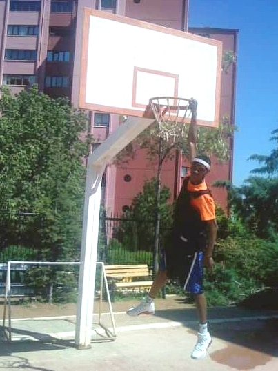 A young teenager uses one arm to hang from the rim of a basketball hoop.