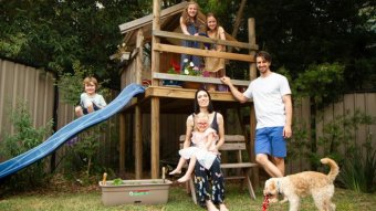 A family stand and sit in front of play equipment with a dog in the foreground.