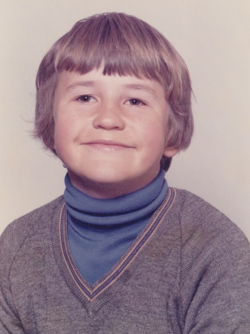 A young boy looks at the camera.