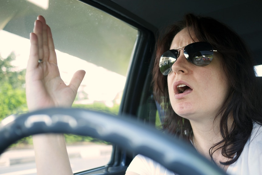 A woman gestures in anger while driving