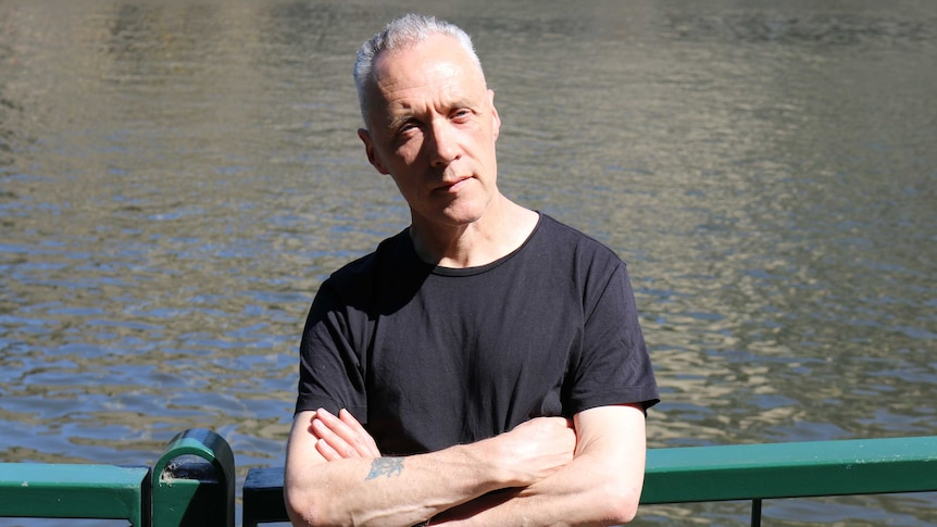 Before a backdrop of water, a man stands against a green railing in black t-shirt, with arms folded, looking forward.