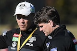 Two Collingwood assistant coaches talk at a Magpies training session.