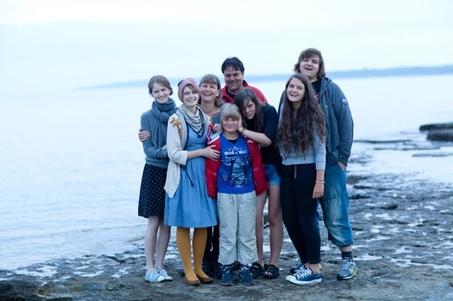 A family of eight pose for a group photo on a beach in Sweden