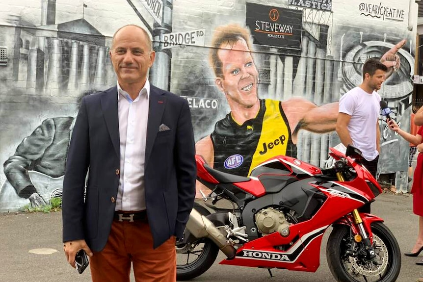 Steve Pantelios standing in front of a Honda motorcycle and a street art mural in Melbourne.
