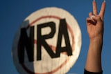 A hand gives a peace sign in front of a round sign with the letters NRA crossed out.