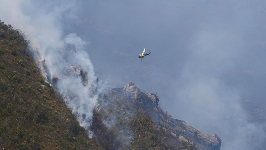 A water-bombing helicopter flies over a fire in south-west Tasmania