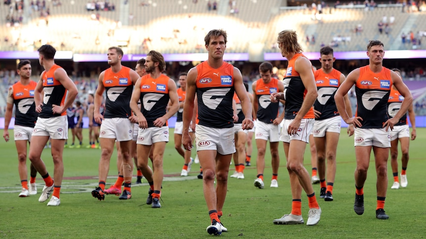 A group of AFL players look around at each other as they wander off the ground.