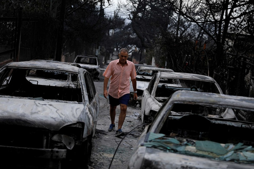 A man walks among burnt cars following a wildfire at the village of Mati.