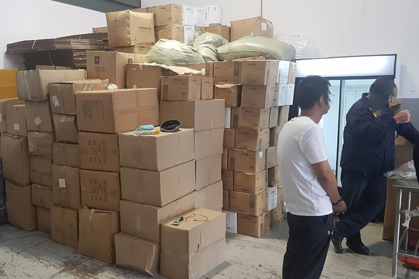 Two men stand near a stack of cardboard boxes.