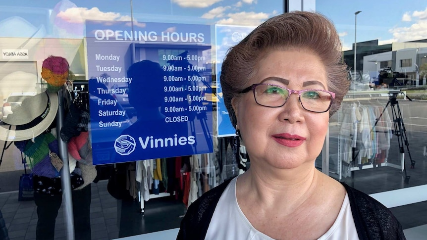 Woman stands in front of glass window of Vinnies store