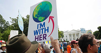 Protester holds sign during climate rally. It shows a globe with words 'I'm with her'