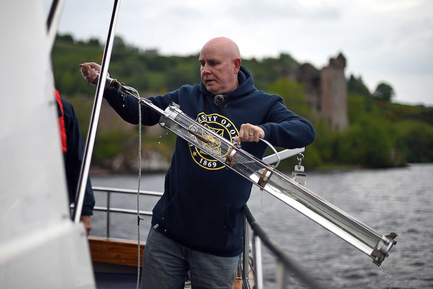 Neil Gemmell, who is standing on a boat, takes a steel rod out of a cylindrical instrument.