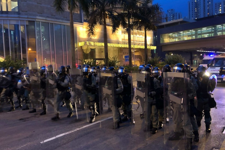 A row of helmeted riot police stand in a street, holding up shields.